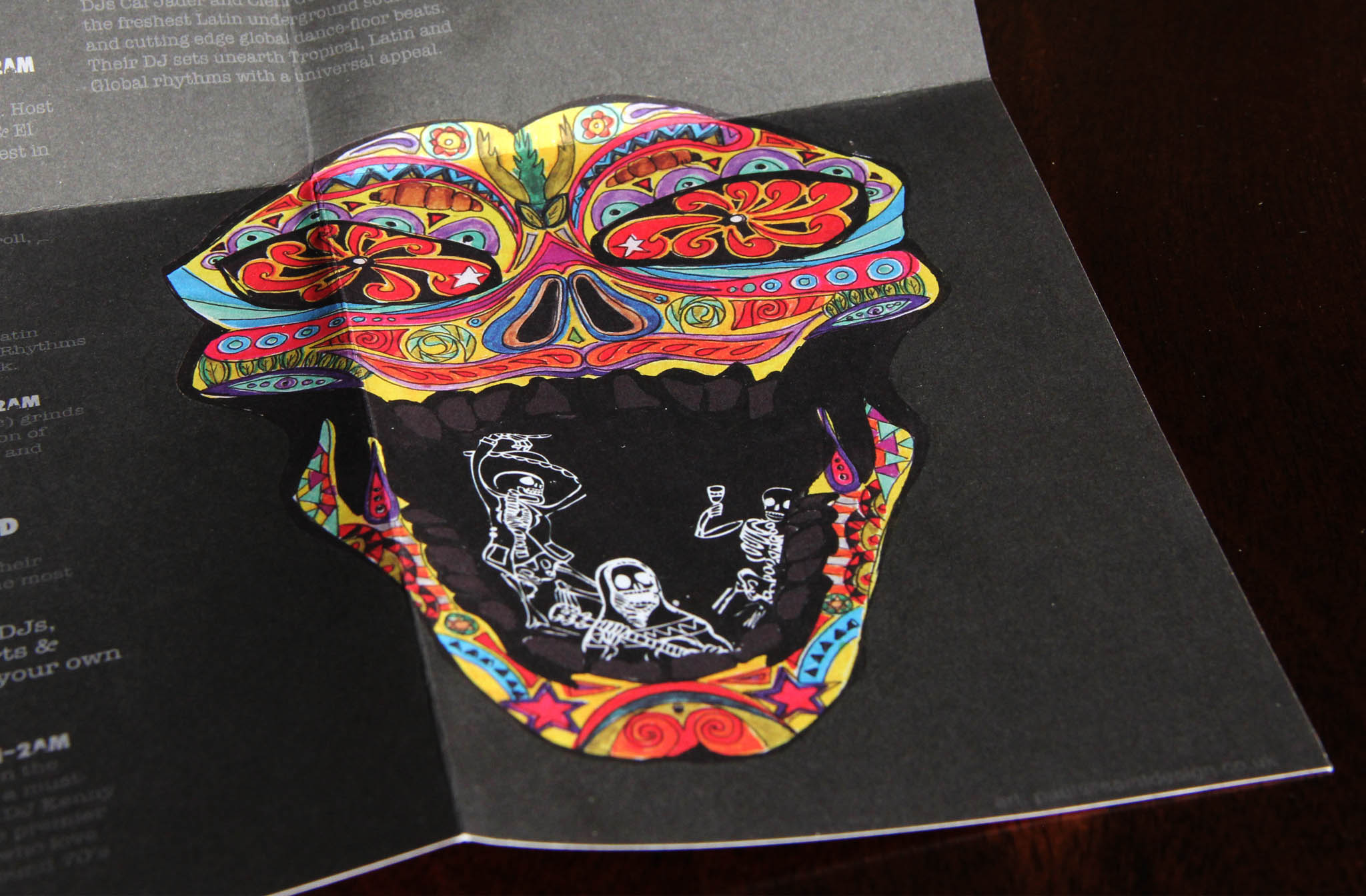 Close-up of a colourful, hand drawn Mexican mask on a black menu, for Chamucos Bar, illustrated by SAINT Design.