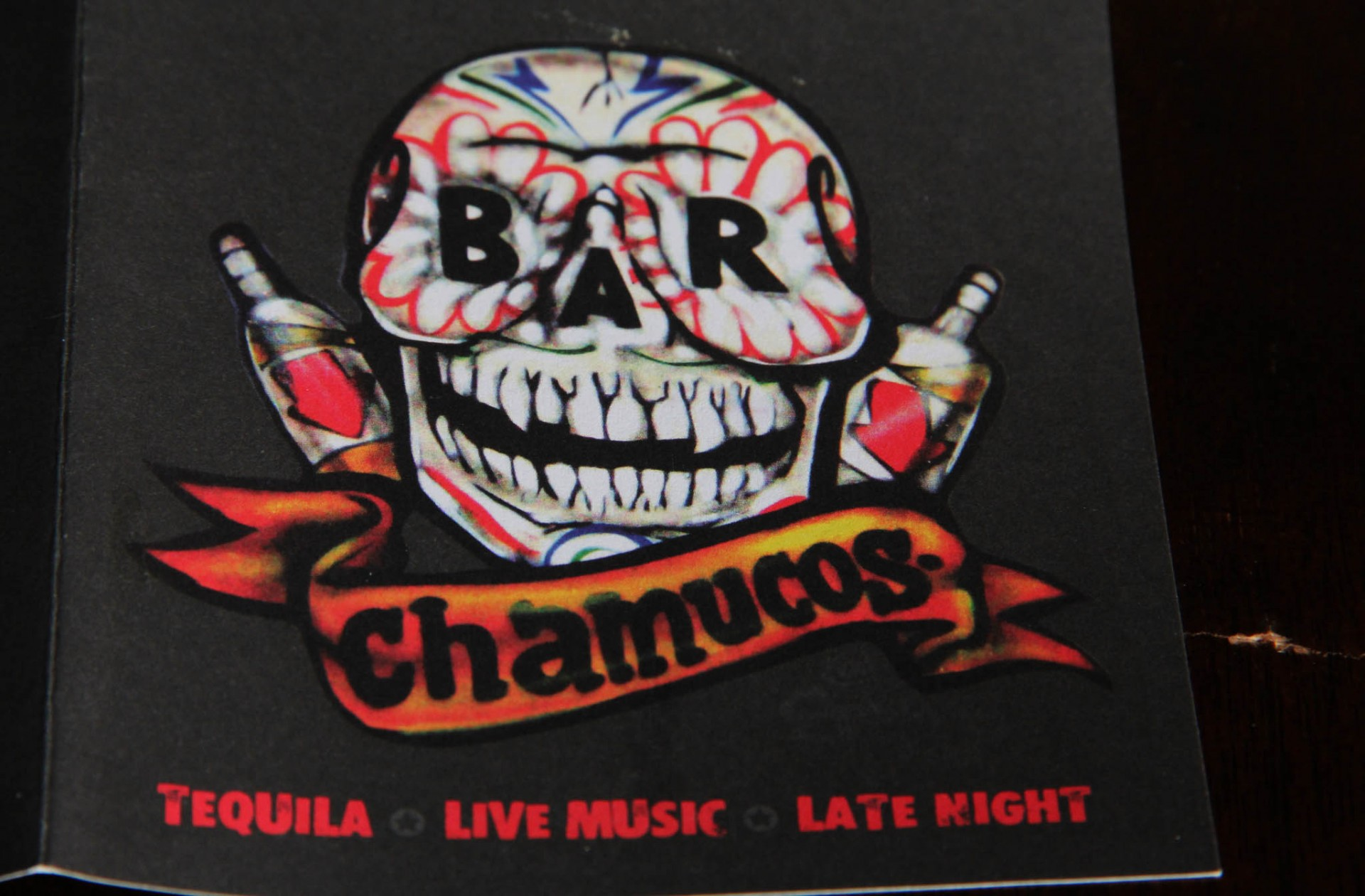 Close-up of a hand drawn Mexican skull on a black drinks menu for Chamucos Bar, Illustrated by SAINT Design.