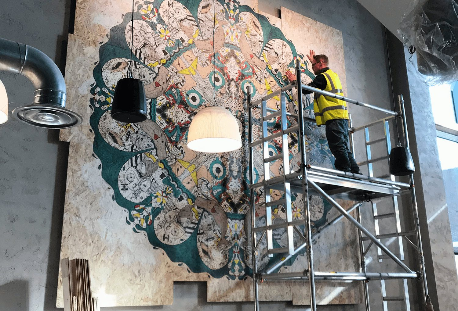 a workman on a tower installing a giant mural