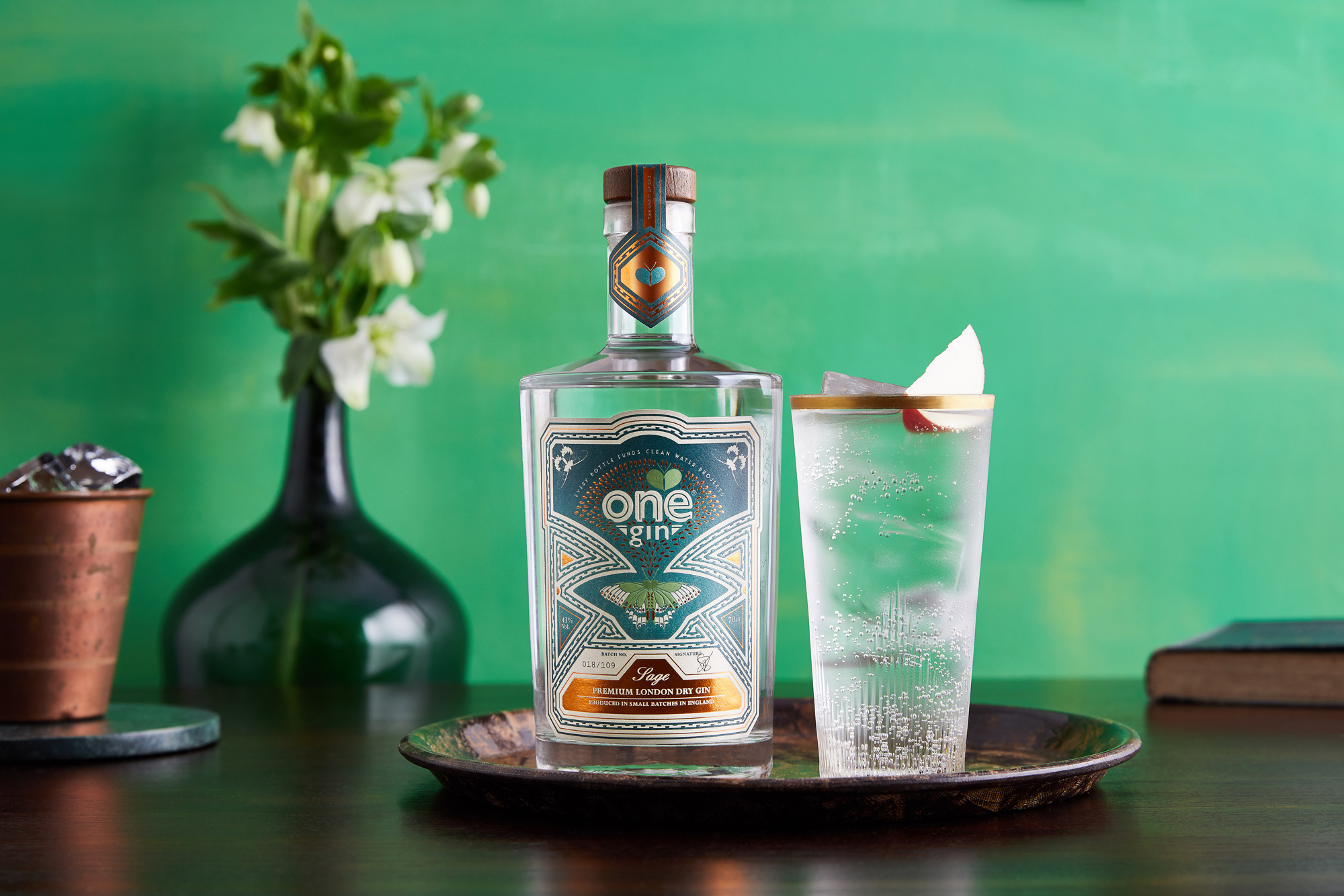 Hero shot of Gin bottle and glass on green background