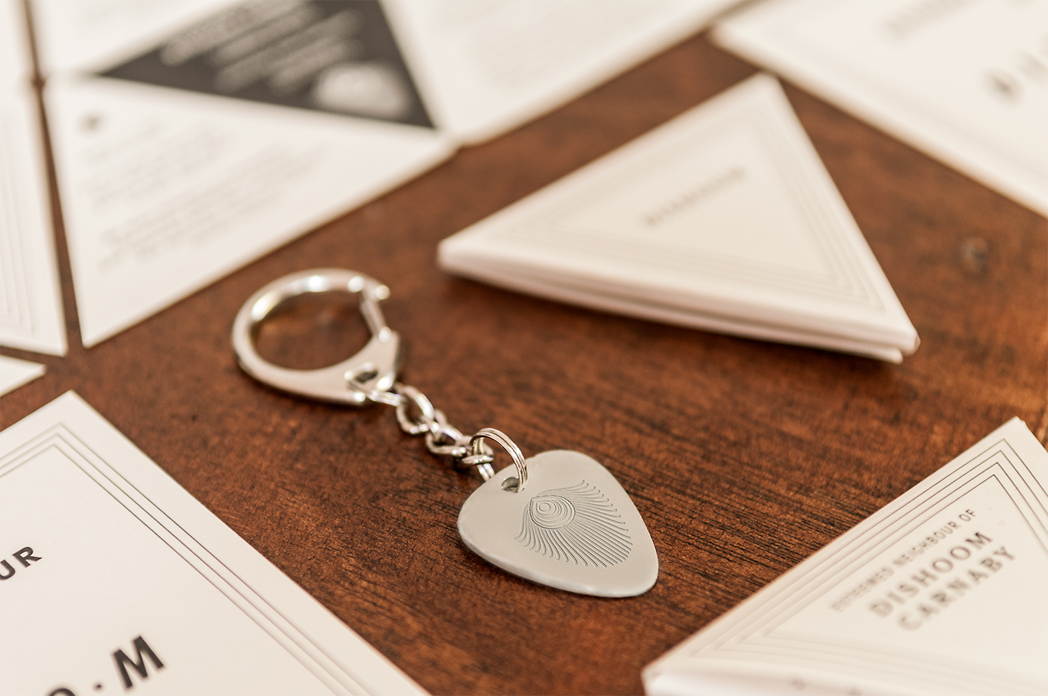 a silver keyring and small triangular envelope on a wooden table