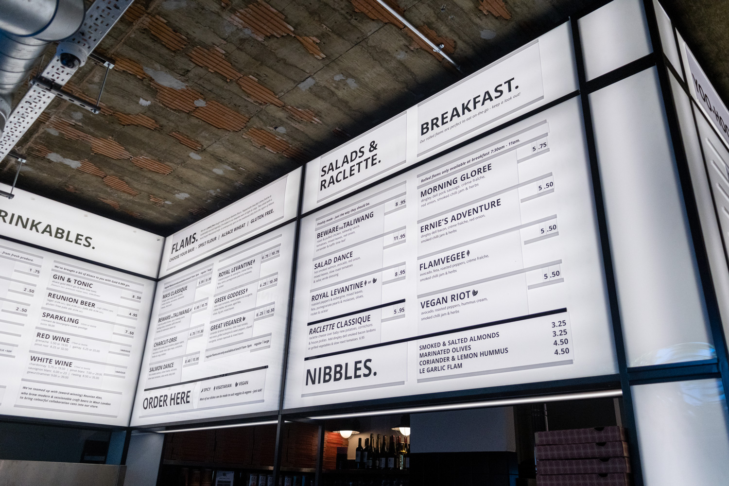 Interior shot of a restaurants black and white internally illuminated menu box with runners showing the menu items in Flamboree, designed by SAINT Design.