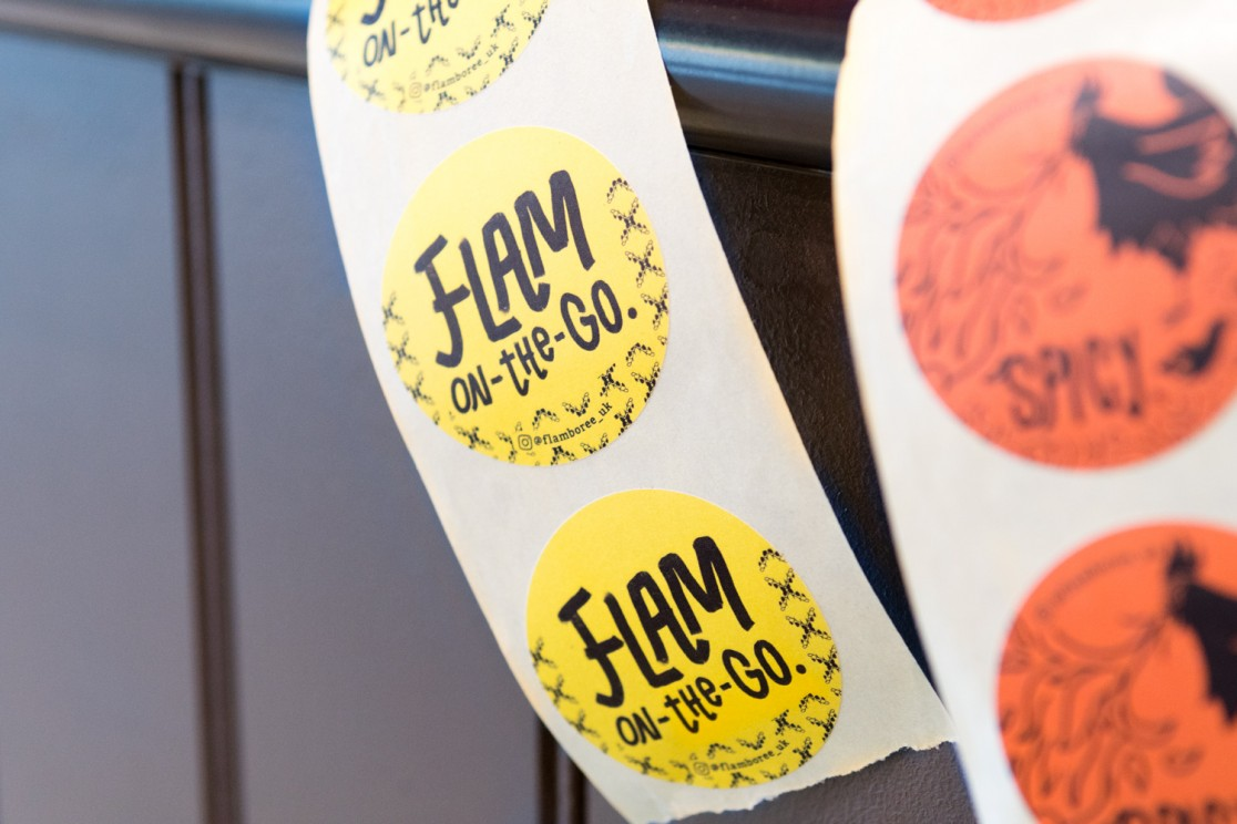 Close-up showing various yellow and orange circular stickers with hand drawn typography on them on a grey wood panelled countertop, in Flamboree, designed by SAINT Design.
