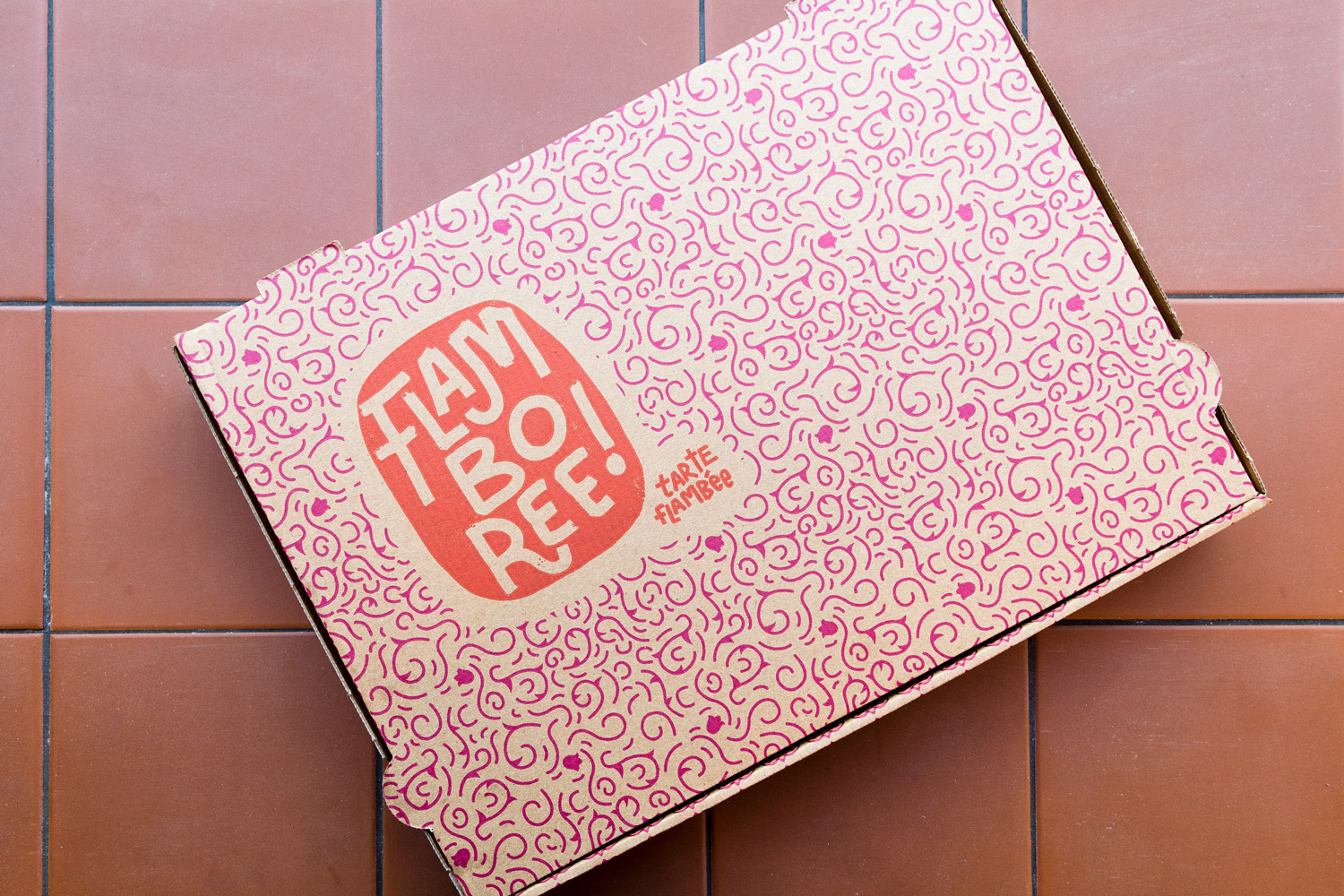 Flat lay showing a pink and red tarte flambée takeaway box with a contemporary floral pattern on it, placed on a tiled terracotta background, in Flamboree, designed by SAINT Design.
