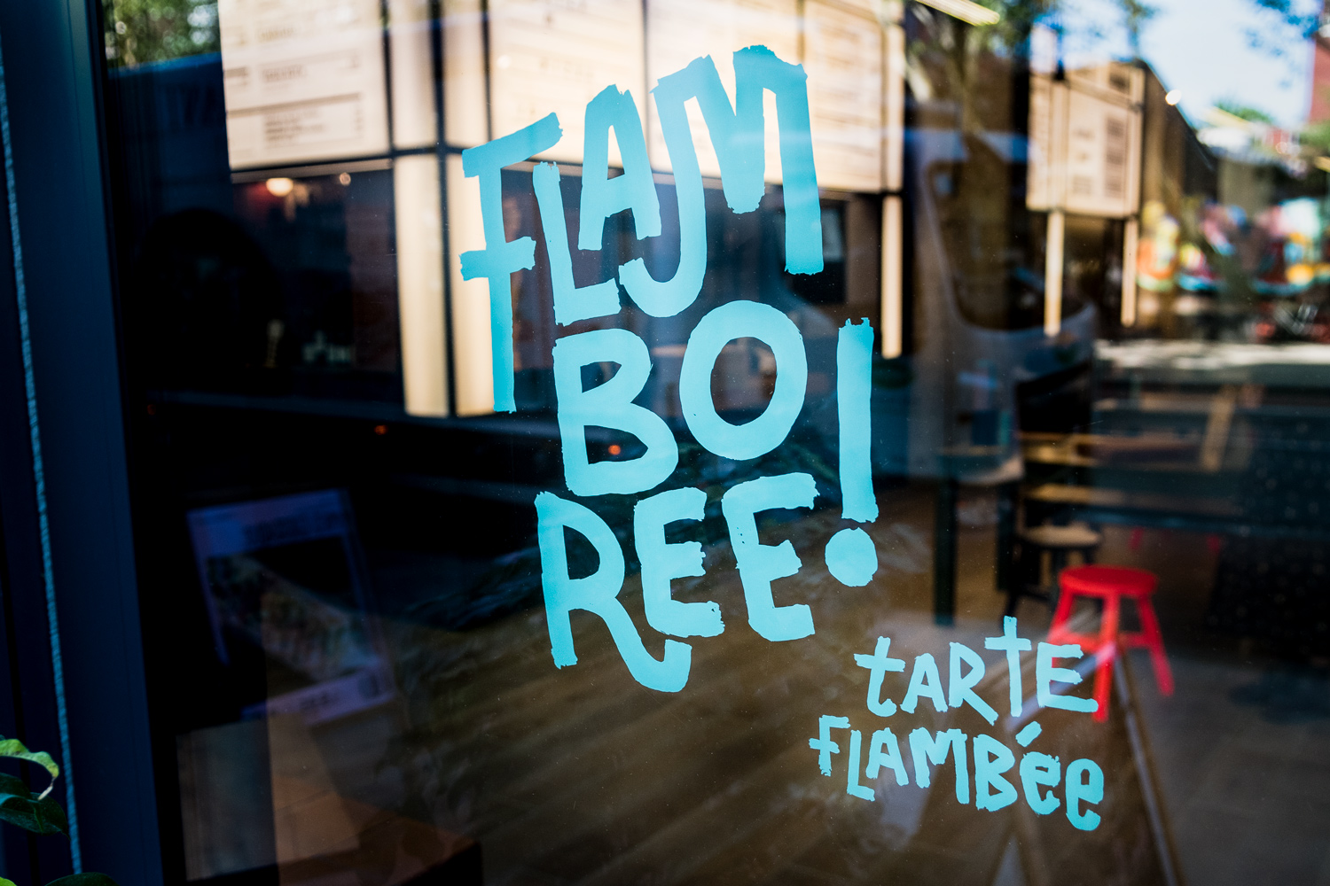 Signwriting in blue of the Flamboree logo onto glass with the restaurant interiors seen in the background.