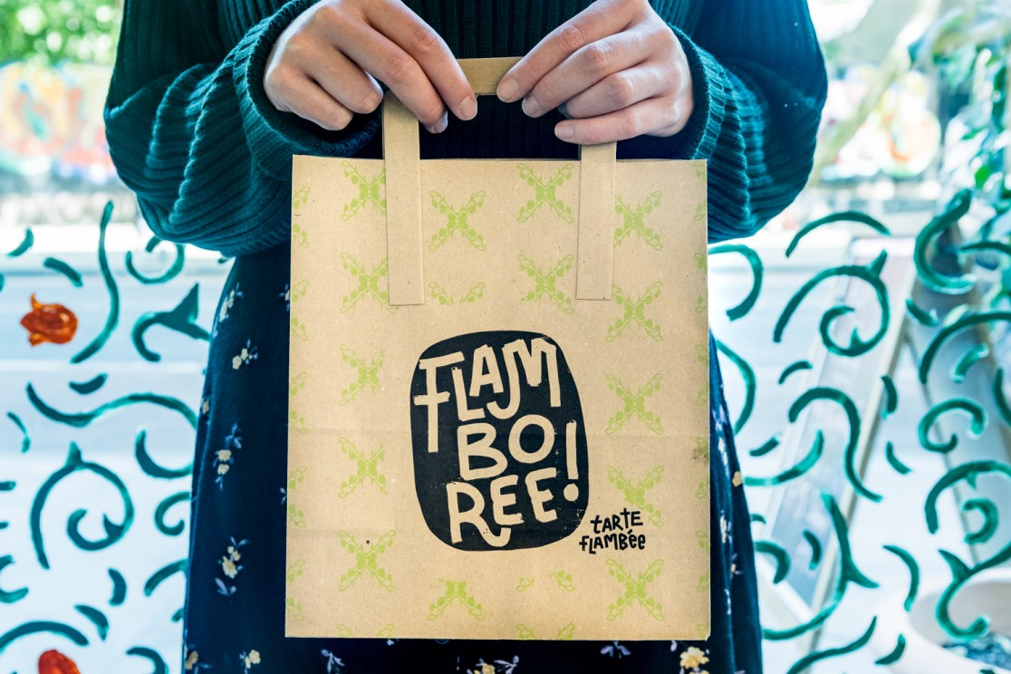 A crop of a girl in a green jumper standing in front of a restaurant window holding a brown paper takeaway bag in Flamboree, designed by SAINT Design.