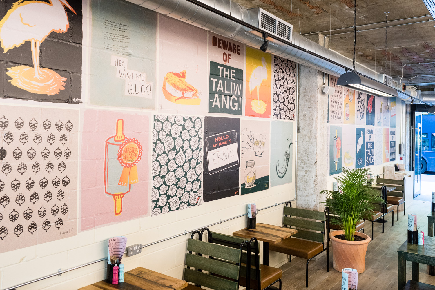 Interior shot of various illustrated fly posters across the wall in the Flamboree restaurant, illustrated by SAINT Design.