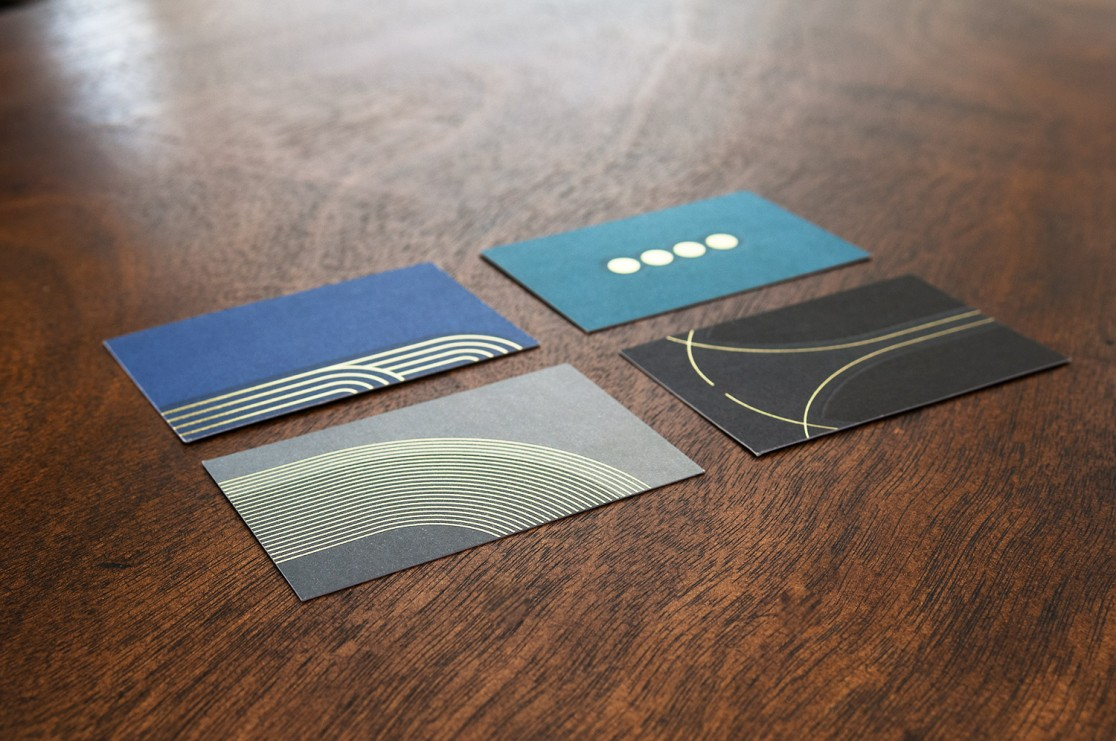 four business cards on a dark wood table