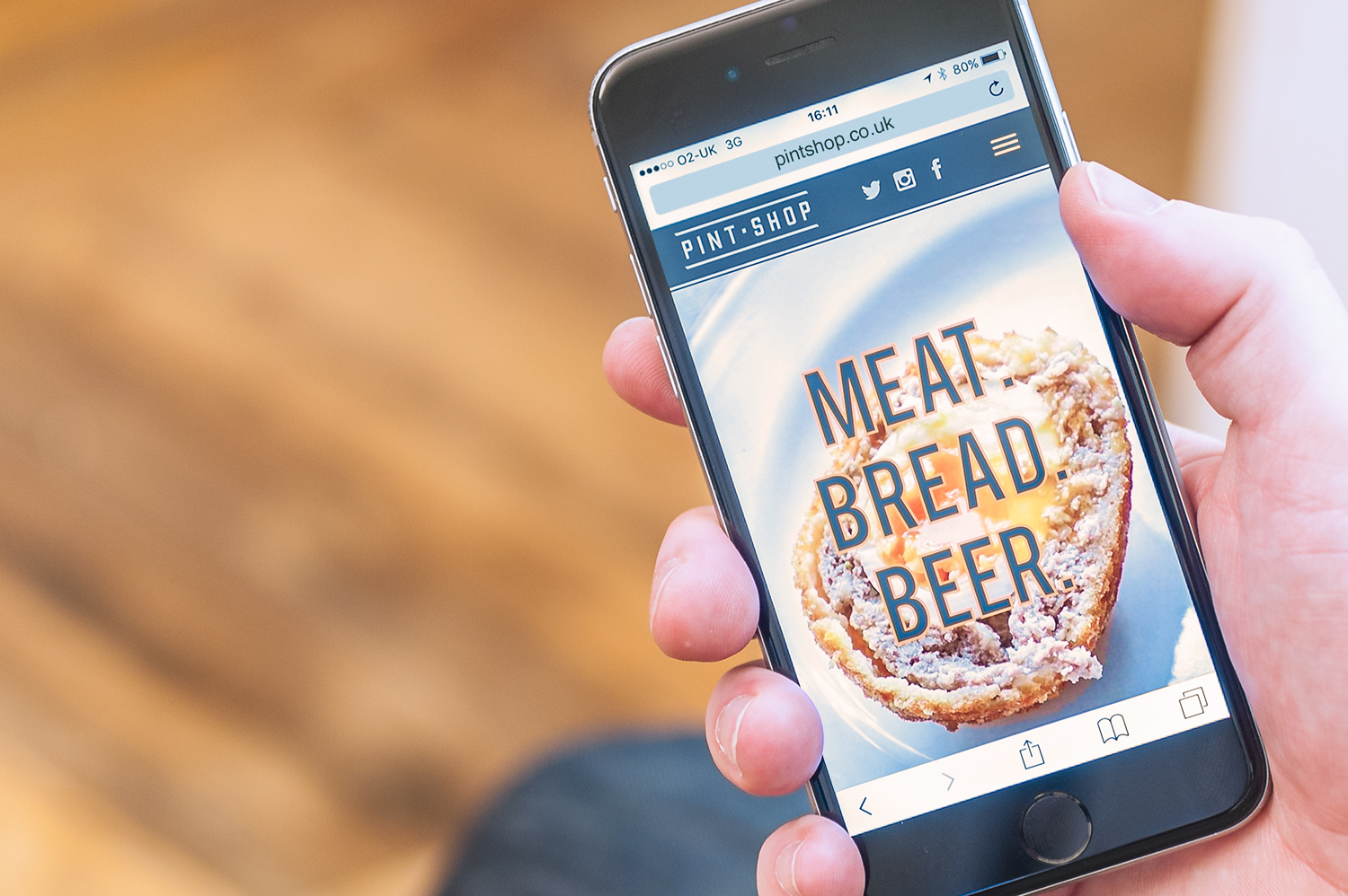 An iPhone being held displaying the Pint Shop mobile website, designed by SAINT Design.