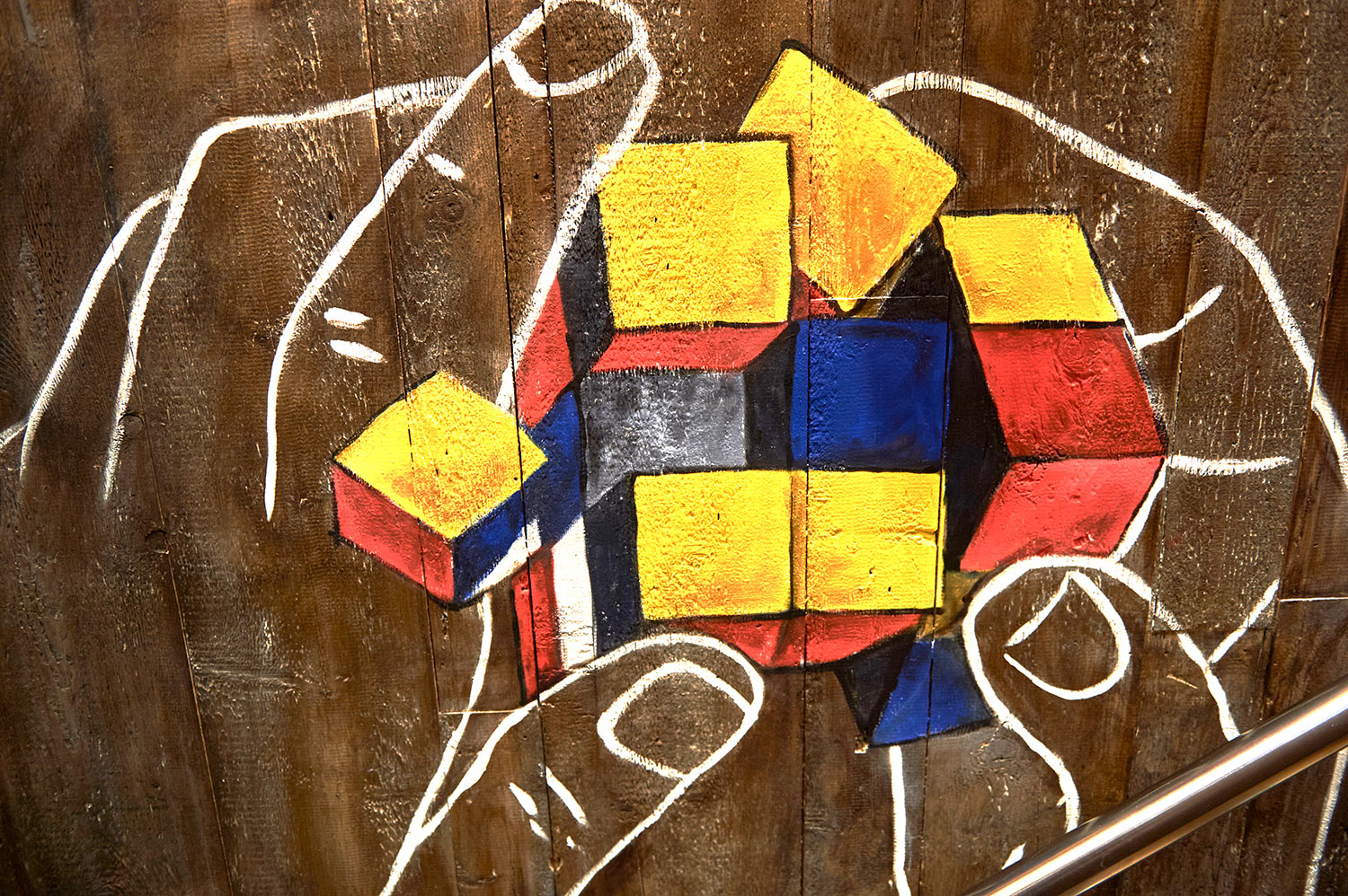 Close-up of a mural showing white outlined hands playing with a rubix cube on a wooden background, in MOD Pizza, Leicester by SAINT Design.