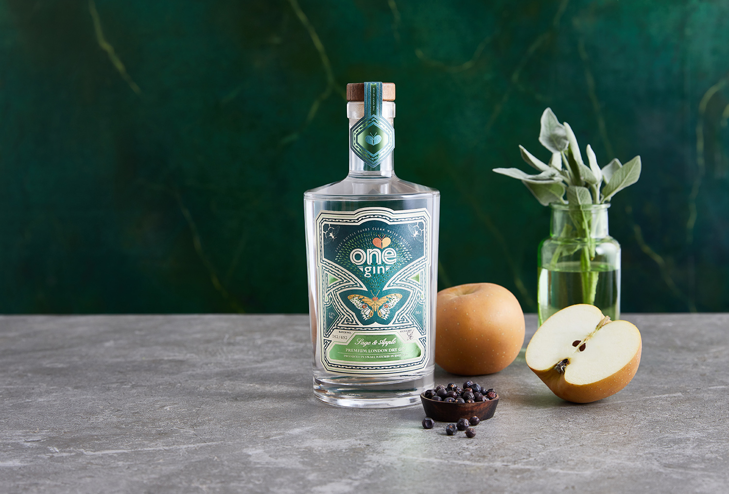 Solo shot of Gin bottle and fruit with dark stone background