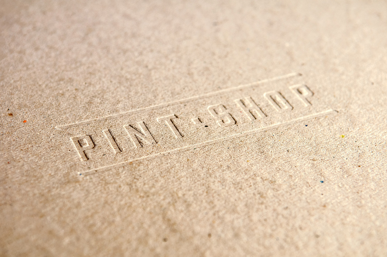 Close-up showing the Pint Shop logo debossed into brown recycled paper, designed by SAINT Design.