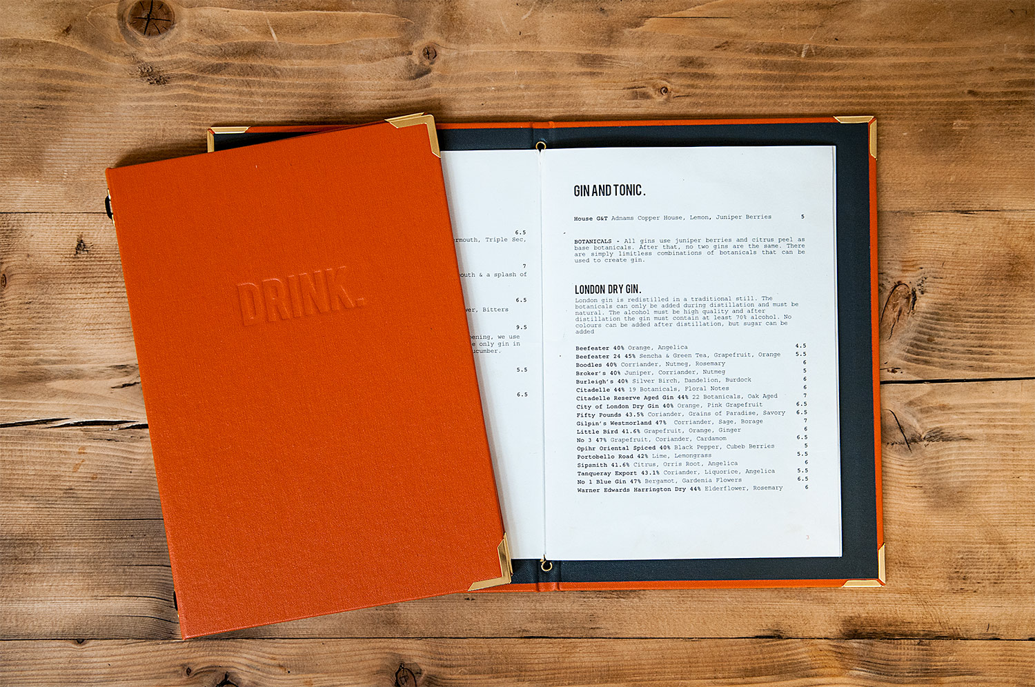 Flat lay of an orange hardback A5 drinks menu with deboss details showing its inners, on a wooden background, for Pint Shop, designed by SAINT Design.