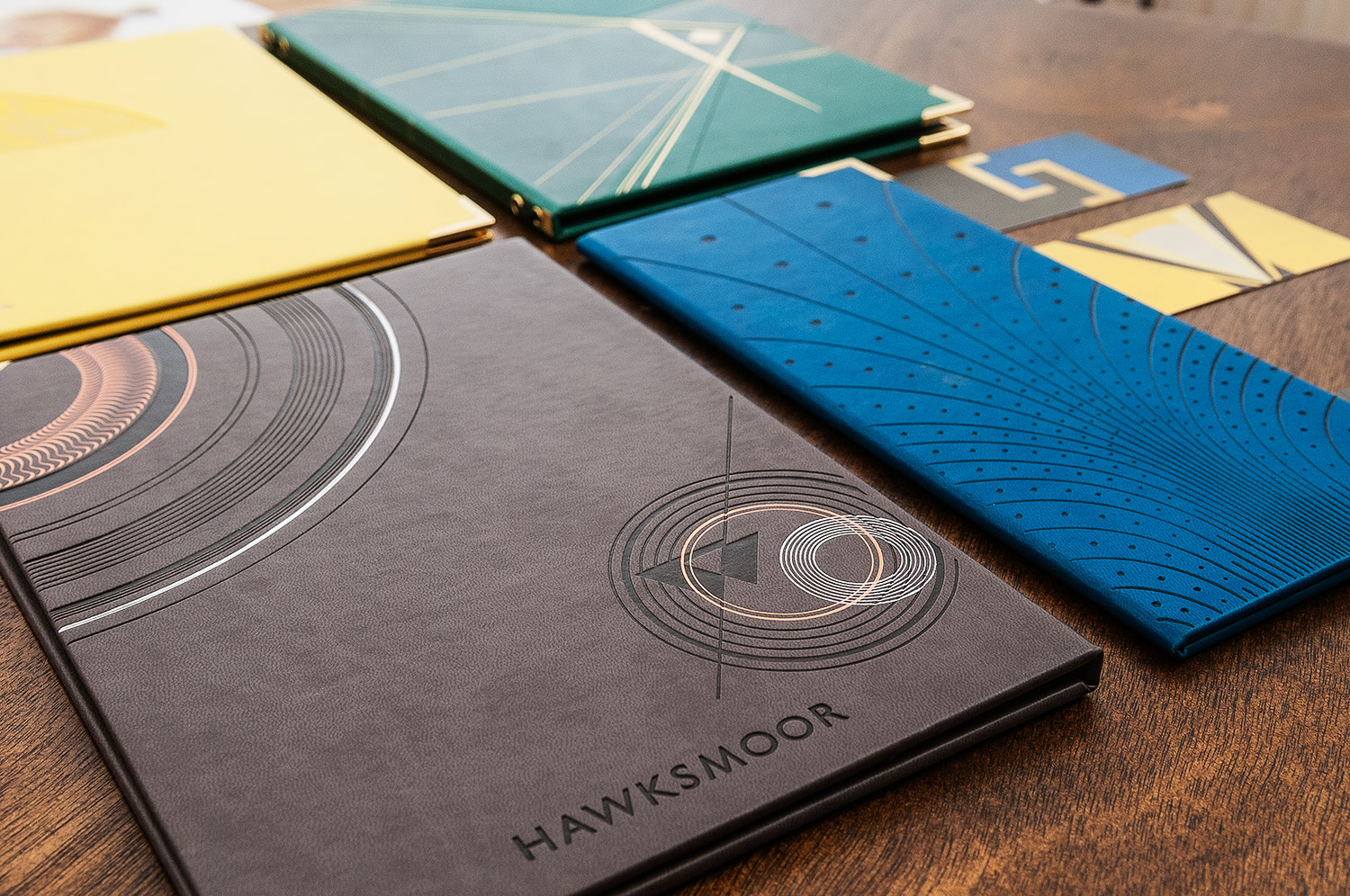 Close-up showing several art deco menu covers in yellow, blue, brown and green, with deboss and foil details, on a dark wood background, for Hawksmoor Air Street, designed by SAINT Design.