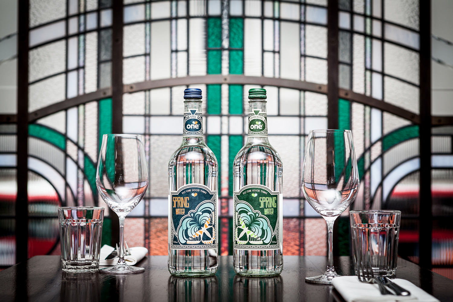 Two glass bottles of One Water in front of an art deco stained glass window on a restaurant table top, designed by SAINT Design.