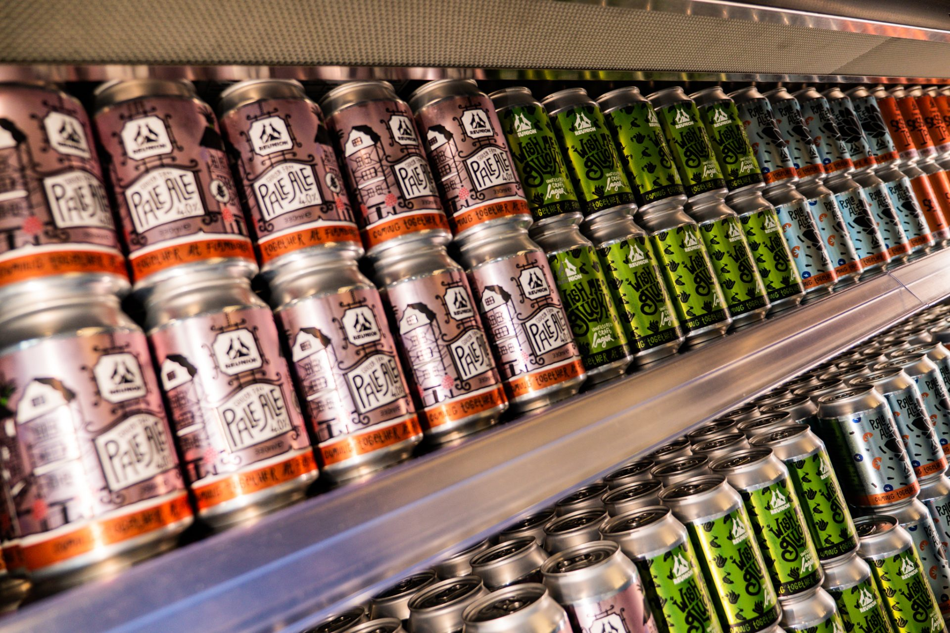 Multiple shot of selection of beer cans with refrigeration background