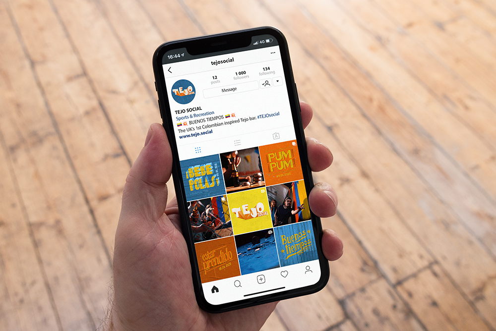 Close-up shot of an iPhone X in hand showing the Instagram feed for Tejo Social, by SAINT Design