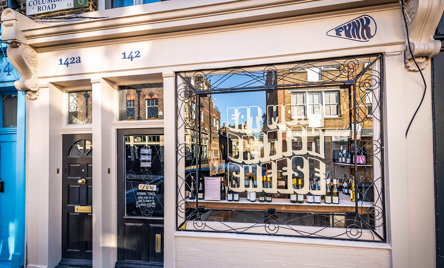 Photography of Funk, a cheese shop on Columbia Road in London, showing the cream cheese coloured front with 70s inspired typography sign written to the window and showing the wordmark hand drawn to the fascia, by SAINT Design.
