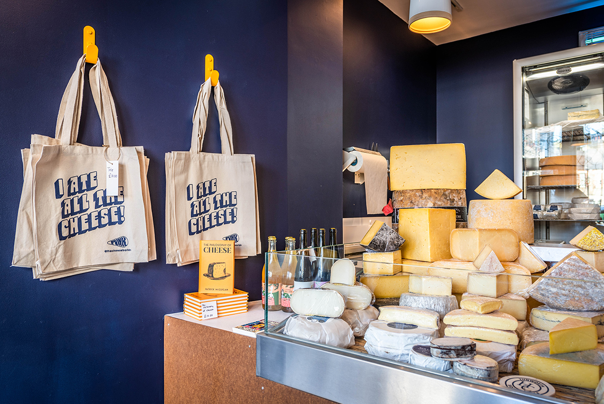 Interior photograph showing the inside of Funk, a cheese shop, showing a fridge full of various cheeses tote bags hanging on the wall, by SAINT Design.