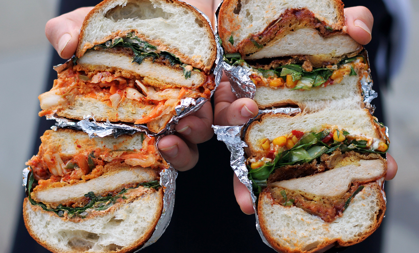Photograph of two delicious vegan chick'n burgers sliced open showing their ingredients and held in two hands, for the vegan dark kitchen Molly Loves Chick'n.
