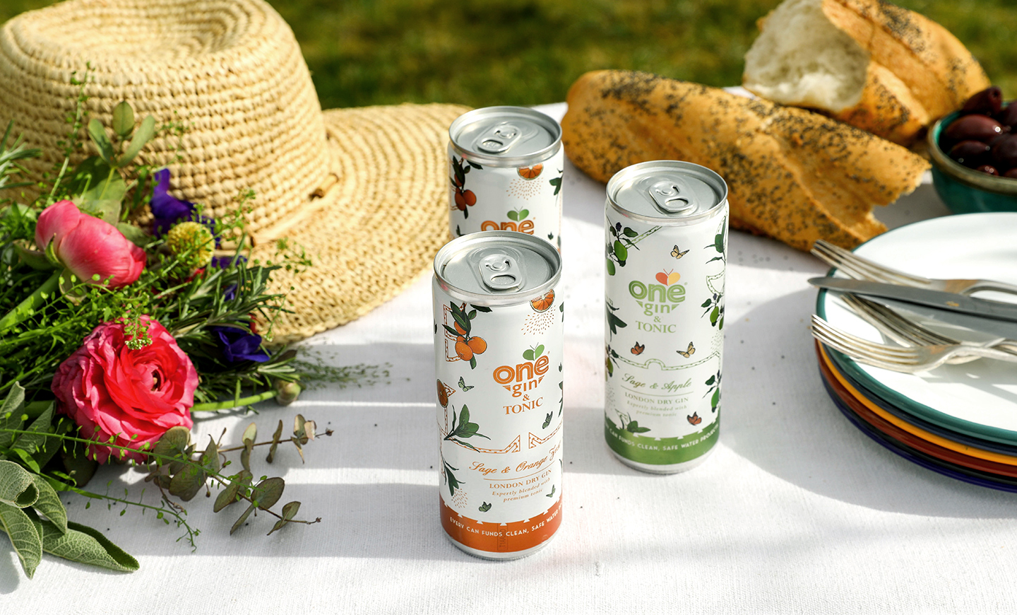 Photograph of three ready to drink gin and tonic cans on a table decorated with food, plates and spring flowers, packaging designed for One Gin by SAINT Design.