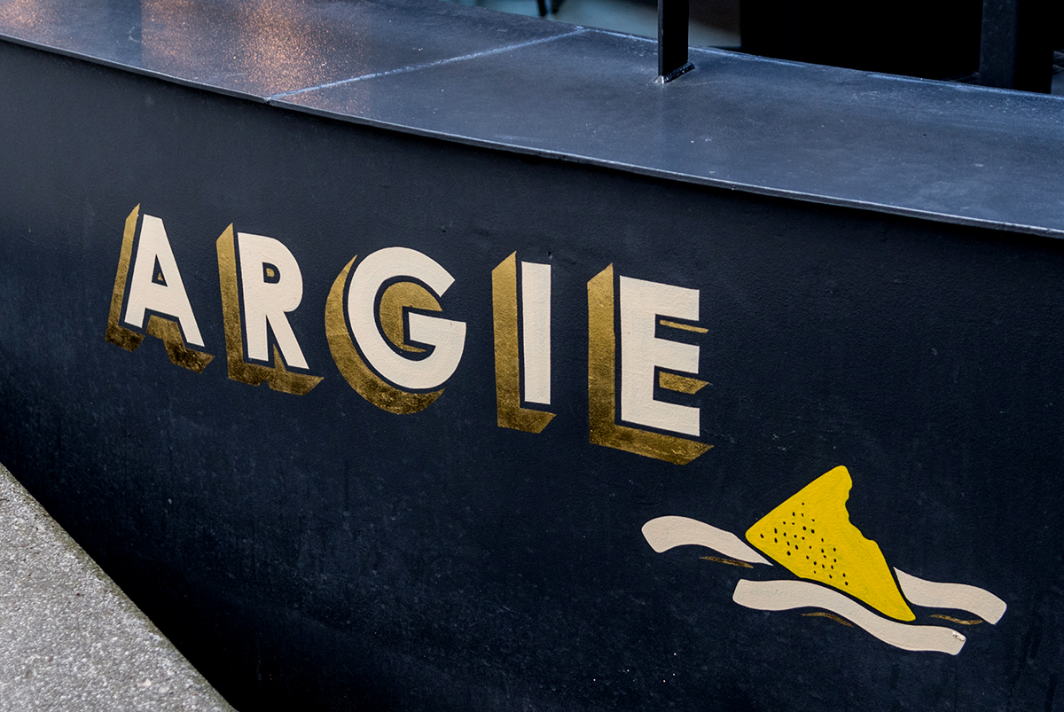 Photography of 3D styled typography in white and gold of the boat name 'Argie', hand painted to the bow of a barge boat in Paddington London, for The Cheese Barge, by SAINT Design.