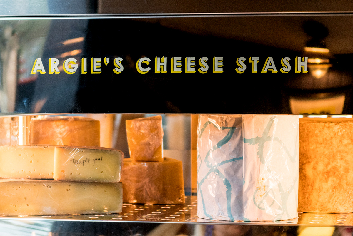 Close-up photography of way finding on the structure of a fridge with cheese in it, showing 3D styled typography in white and yellow, stating 'Argie's Cheese Stash', for The Cheese Barge, by SAINT Design.