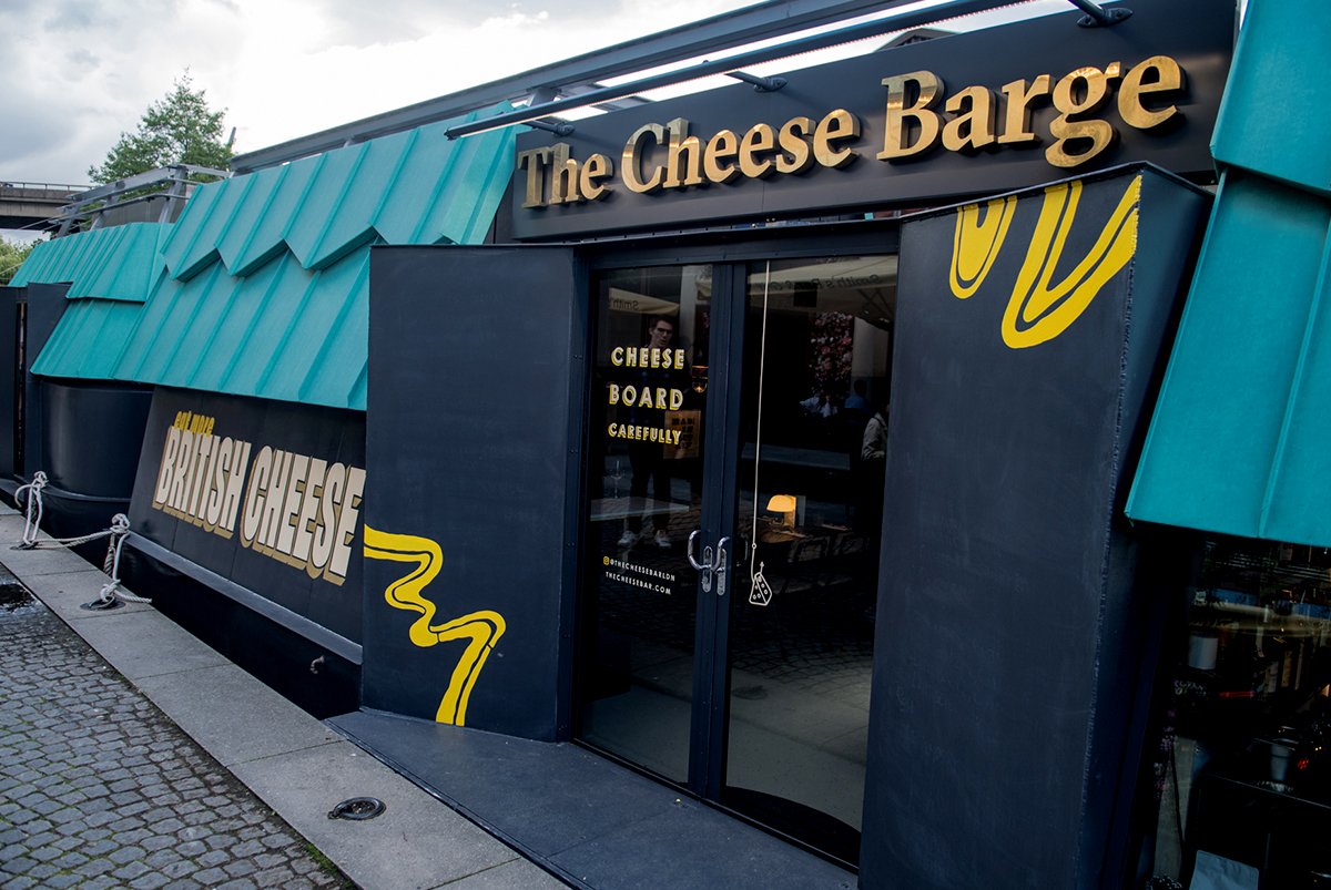Photography showing hand painted signage on the the front doors and of the side of a barge boat for The Cheese Barge, a restaurant in Paddington, by SAINT Design.