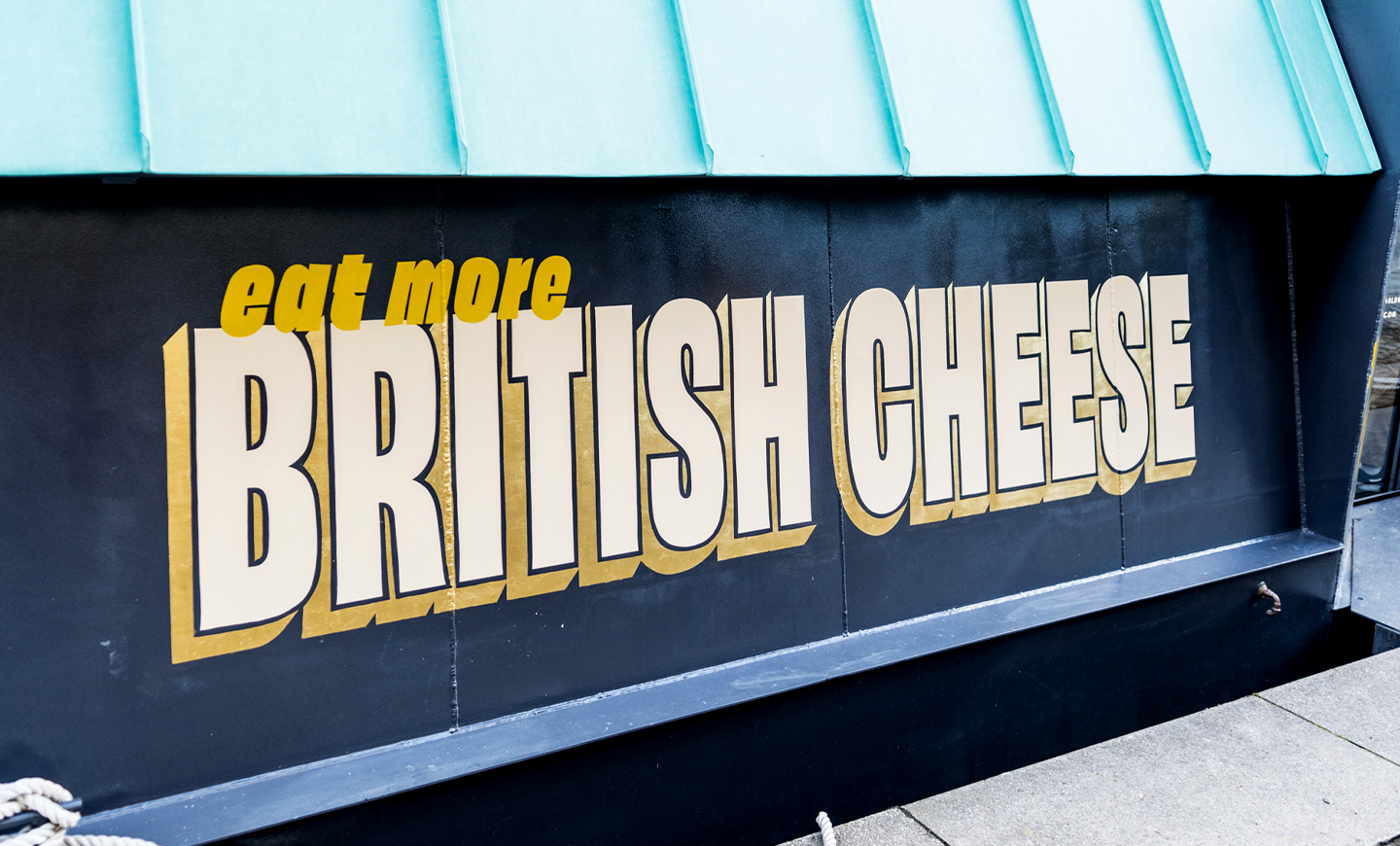 Photography of contemporary 3D styled typography in white, gold and yellow saying 'Eat More British Cheese' hand painted to the side of a barge boat restaurant in Paddington London, for The Cheese Barge, by SAINT Design.