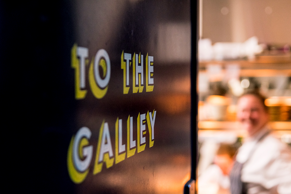 Close-up photography of way finding to the kitchen on a dark door, showing 3D styled typography in white and yellow, stating a nautical pun, for The Cheese Barge, by SAINT Design.