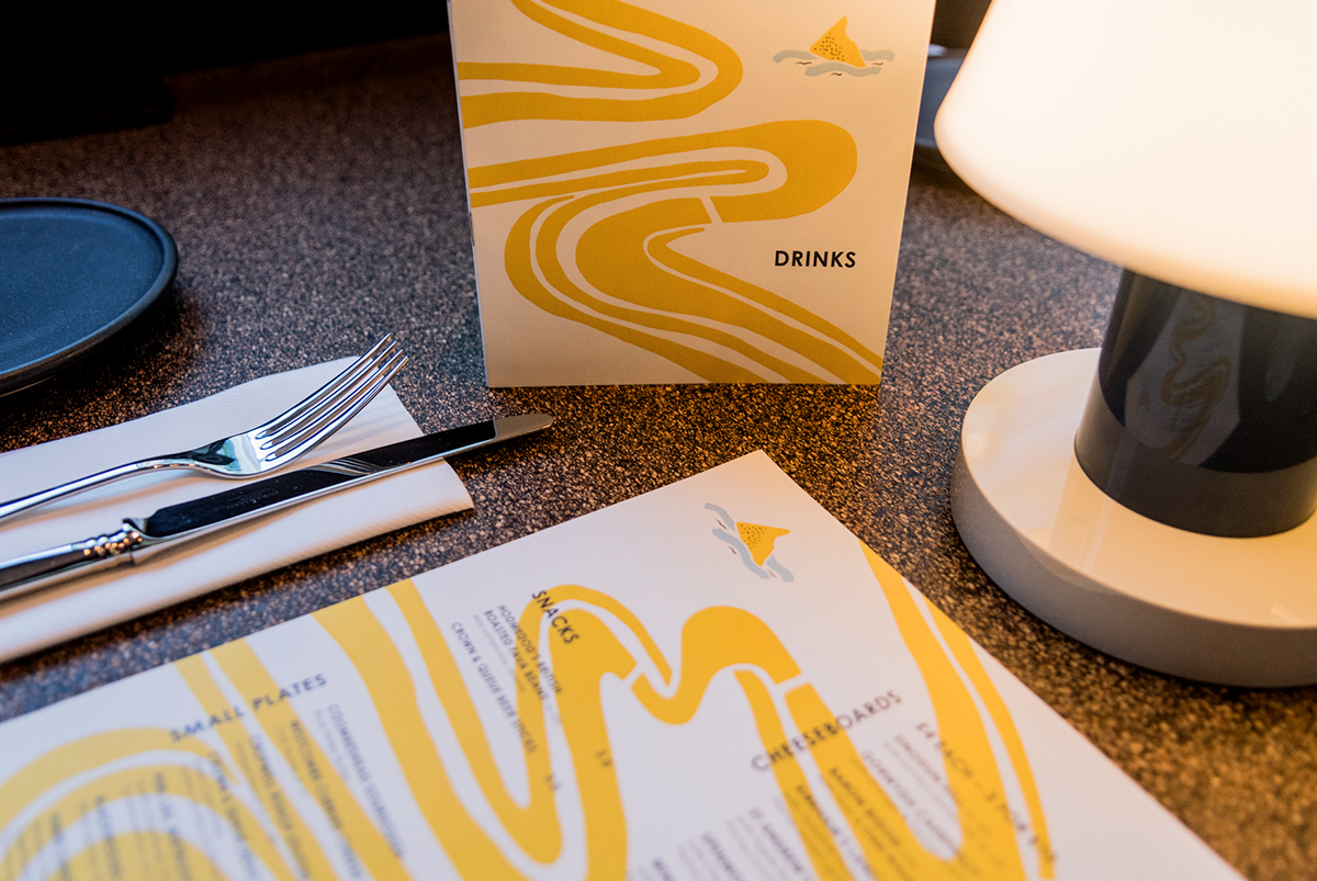 Photography of menus in a table setting in a restaurant, designed for The Cheese Barge, by SAINT Design.
